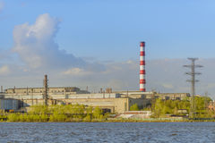 Metallurgical plant near pond on a background of blue sky. Metallurgical plant near a pond on a background of blue sky Stock Photo