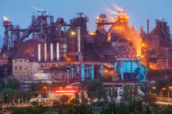 Metallurgical plant with white smoke at night. Steel factory with smokestacks . Steelworks, iron works. Heavy industry Royalty Free Stock Image