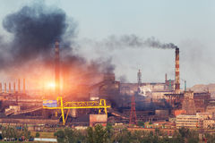 Metallurgier planterar i Ukraina på solnedgången Stålfabrik med smog Arkivbild