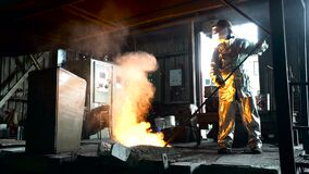 Metallurgist Job Worker In A Steel Plant Hot Molten Metal Pouring. Heavy Industry Worker Working Hard.