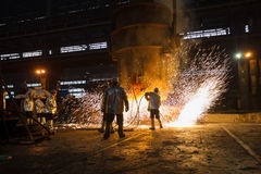 Metallurgist at work in heavy industry factory. Some metallurgist working near molten metal boiler preparing a piece of metal casting in heavy industry factory Stock Photos