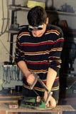 Metallurgists som sågar brons Arkivfoto