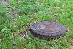 Metallvattenlucka i gräset, på bakgrunden av gräs royaltyfri bild