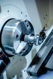 Metallworkpiecen som klämmas fast i drejbänken, kastar CNC-maskinen Arkivbild