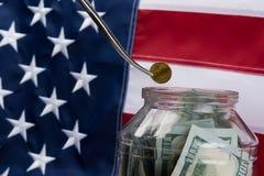 Metallzange setzte eine Münze in ein Glas mit dem Geld auf Hintergrund der Flagge ein Lizenzfreie Stockfotos