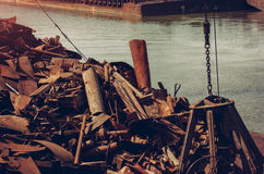 Metals recycling close up. Metal claw relocate scrap metal, with tow in the background Royalty Free Stock Images