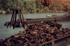 Metals recycling cranes metal claw. Metals recycling on a river bank with freighter in a background Stock Photos