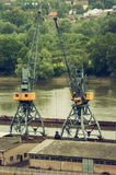 Metals recycling cranes metal claw. Metals recycling cranes on the riverbank with freighter in a background Royalty Free Stock Images