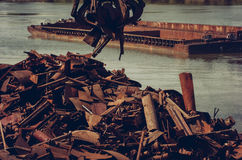 Metals recycling on a riverbank. Metal claw relocate scrap metal, with tow in the background Stock Image