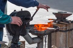 Metalsmith blowing air on the fire Royalty Free Stock Photography