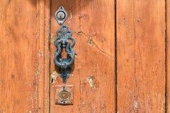 Metalu doorknocker na wietrzejącym drewnianym drzwi zdjęcia stock