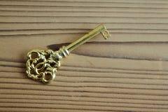 Metalu klucz na drewnianym tle w antykwarskim spojrzeniu Fotografia Stock