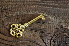Metalu klucz na drewnianym tle w antykwarskim spojrzeniu Obrazy Stock