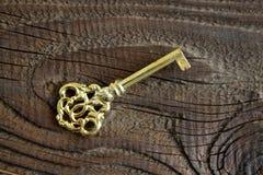 Metalu klucz na drewnianym tle w antykwarskim spojrzeniu Zdjęcia Royalty Free