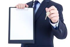 Metalu kluczowy i pusty schowek w męskich agent nieruchomości rękach jest Zdjęcia Royalty Free