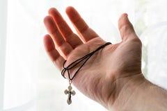 Metalu krzyż w ręce z ostrością na ręce Fotografia Stock