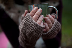 Metalu kubek z gorącą herbatą w ręki w ciepłe wygodne mitynki Obraz Stock