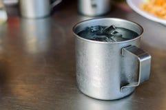 Metalu szkło lub filiżanka zimna woda z lodem na stal nierdzewna stołu tle fotografia stock
