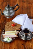 Metalu talerz z crispbread, ser, chałupa ser, baleron, czereśniowy pomidor, filiżanka kawy, kawowy garnek na drewnianym obrazy stock