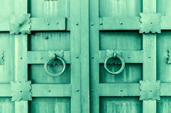 Metalu zielony rocznik textured drzwi z pierścionek drzwiowymi rękojeściami i metali szczegółami w formie stylizowani kwiaty Zdjęcie Stock