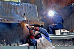 Metalwork construction of large tubes with workers working welding machine Royalty Free Stock Photography