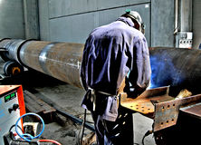 Metalwork construction of large tubes with workers working welding machine Stock Images