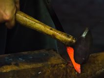 A metalworker shapes a piece of iron 3. A metalworker beats a glowing piece of iron into the home decoration shape he desires on his anvil with his hammer at a Royalty Free Stock Photography