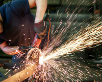 Metalworker cutting a steel bar Royalty Free Stock Images