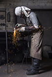 Metalworker cutting on steel plate creating sparks, cutting iron. Young metalworker cutting on steel plate creating sparks, cutting iron with laser in workshop Royalty Free Stock Images