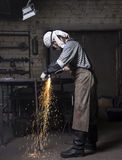 Metalworker cutting on steel plate creating sparks, cutting iron. Young metalworker cutting on steel plate creating sparks, cutting iron with laser in workshop Stock Images
