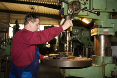 Metalworker on a drilling machine. A metalworker drilling a workpiece Royalty Free Stock Images