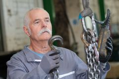 Metalworker hooks steel tube to lift. Metalworker hooks a steel tube to lift Stock Images