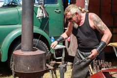 A metalworker at an outdoor forge stock image