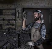 Metalworker preparing for work. Senior Metalworker preparing for work with iron Stock Photos
