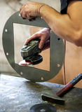 Metalworker sanding a metal component Royalty Free Stock Photo