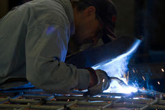Metalworker at work. In his workshop using the welder Stock Photo