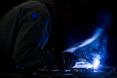 Metalworker at work. In his workshop using the welder Stock Images