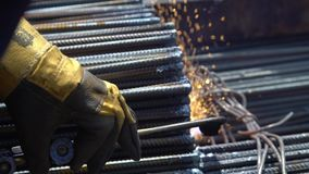 Metalworker worker processes metal rods with welding machine closeup stock footage