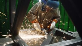 Metalworker working with angle grinder. Lots of sparks flying stock footage