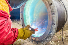Metalworker working on a pipeline. Welder welding a pipe on a terrain Royalty Free Stock Image