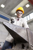 Metalworker works metal with hammer on the anvil Royalty Free Stock Photo