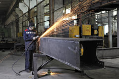 Metalworkers polishing welds metal structures, producing fountai Royalty Free Stock Image
