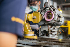 Metalworking industry: finishing metal working on lathe grinder machine Royalty Free Stock Image