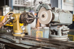 Metalworking industry: finishing metal working on lathe grinder machine Royalty Free Stock Photography