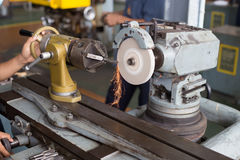 Metalworking industry: finishing metal working on lathe grinder machine. With flying sparks Royalty Free Stock Photography