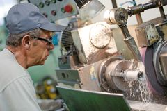 Metalworking industry: operator man worker at horizontal rotary grinding machine Royalty Free Stock Photography