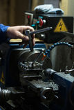 Metalworking. Man operating a small lathe machine in a craftsman worshop. Metalworking. Man operating a small lathe in a craftsman worshop royalty free stock image