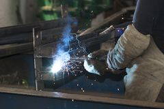 Metalworking shop workers work behind machines and apparatuses to create steel structures Royalty Free Stock Photo