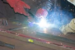 Metalworking shop workers work behind machines and apparatuses to create steel structures Stock Photo