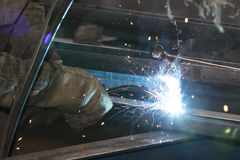 Metalworking shop workers work behind machines and apparatuses to create steel structures Stock Photos
